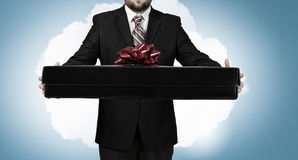 Businessman hold gift box . Mixed media Stock Image