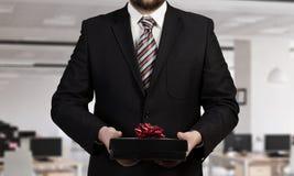 Businessman hold gift box . Mixed media Royalty Free Stock Photo