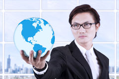 Businessman hold globe in hand - indoor. Asian businessman looking smart with glasses holding a globe Royalty Free Stock Photography