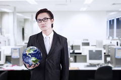 Businessman hold globe at office. Confident asian businessman holding a globe in the office Stock Images