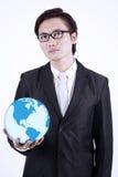 Businessman hold globe on white background. Confident asian businessman holding a globe, isolated on white Stock Image