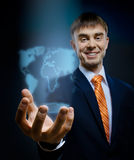 Businessman. Hold in hand terrestrial globe, on dark blue background,  business concept Royalty Free Stock Photography