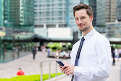 Businessman hold with mobile phone at outdoor Stock Images