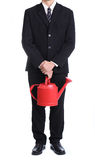 Businessman hold red watering pot Royalty Free Stock Photos