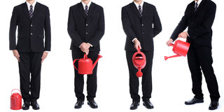 Businessman hold red watering pot Royalty Free Stock Photo