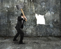 Businessman hold sledgehammer cracking big white hole on concret Stock Photo