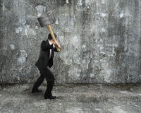 Businessman hold sledgehammer to crack old mottled concrete wall Stock Photos