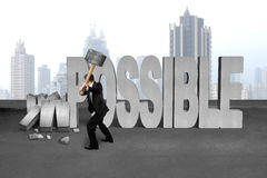 Businessman hold sledgehammer to smash impossible 3D concrete word. On cement floor and city skyscraper background royalty free stock photo
