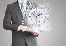 Businessman hold tablet pc with clock and gears Royalty Free Stock Photo