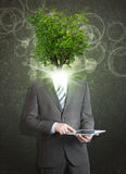 Businessman hold tablet pc. Green tree instead his Stock Photo