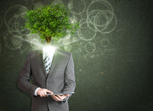 Businessman hold tablet pc. Green tree instead his Stock Photography