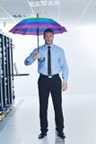 Businessman hold umbrella in server room Stock Photo