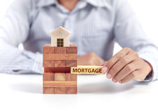 Businessman hold word mortgage on puzzle with wooden home model Stock Images