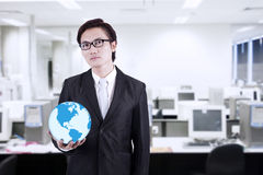 Businessman hold world globe at office. Confident asian businessman holding a globe in the office Royalty Free Stock Photography