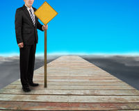 Businessman hold yellow board standing on wooden way Stock Photos
