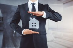 Accomodation, hotel and real estate concept. Businessman holding abstract house icon on blurry bedroom background. Accomodation, hotel and real estate concept royalty free stock photography
