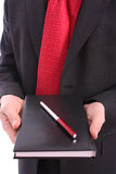 Businessman holding agenda and red pen Royalty Free Stock Photo