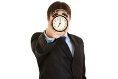 Businessman holding alarm clock in front of face Royalty Free Stock Image