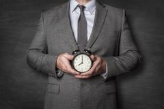 Businessman holding alarm clock in front of him stock image