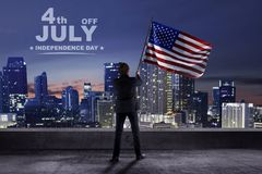 Businessman holding american flag on the terrace building. Happy Independence Day royalty free stock images