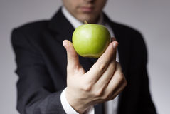 Businessman holding apple. A view of the hand of a businessman holding a fresh green apple Stock Photo