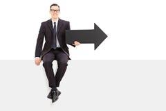 Businessman holding an arrow seated on a panel Stock Photos
