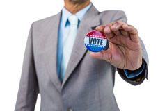 Businessman holding a badge. On white background Royalty Free Stock Photos