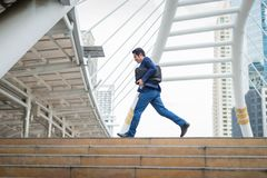 Businessman holding bag and running rapidly in the city. concept of rush hour and late for work. Stock Photos