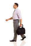 Businessman holding bag walking Stock Photography
