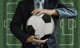 Businessman holding the ball. On a black background Stock Photos