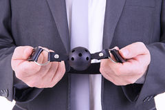 Businessman holding ball gag. Isolated on white background Stock Photography