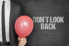 Businessman Holding Balloon By Dont Look Back Text On Blackboard Stock Image