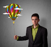 Businessman holding a balloon drawing Royalty Free Stock Photos