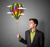 Businessman holding a balloon drawing Stock Images