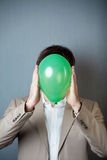 Businessman Holding Balloon In Front Of Face Against Blue Wall Stock Image