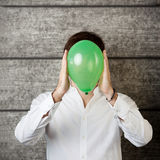 Businessman Holding Balloon In Front Of Face Against Wooden Wall Stock Photo