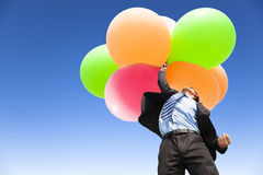 Businessman holding balloons and flying up Royalty Free Stock Photos