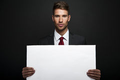 Businessman holding banner with copy space Stock Images
