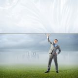 Businessman holding a banner with one hand Stock Photography