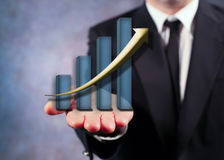 Businessman Holding Bar Graph And Arrow. Businessman Holding Arrow And Bar Graph On His Hand Royalty Free Stock Photo
