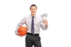 Businessman holding a basketball and money Stock Images