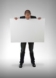 Businessman holding a big card Stock Images