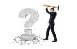 Businessman holding big hammer to crash question mark made of stone Stock Photography
