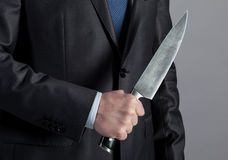 Businessman holding big knife Stock Images