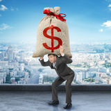 Businessman holding big moneybag Stock Photography