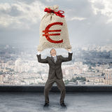 Businessman holding big moneybag with euro sign Stock Photos