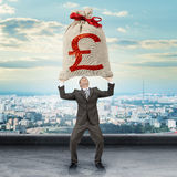 Businessman holding big moneybag with pound sign. With city view stock images