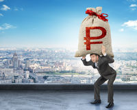Businessman holding big moneybag with ruble sign Stock Photo