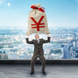 Businessman holding big moneybag with yen sign Royalty Free Stock Image