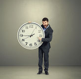 Businessman holding big white clock Royalty Free Stock Photography